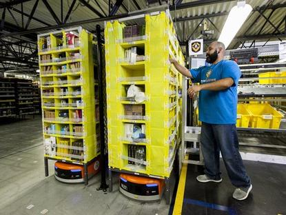 An Amazon employee takes items delivered on pods transported by Kiva mobile robots. The online retailing giant said its Kiva fleet has topped 15,000 units head of the holiday season.