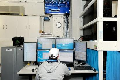 An IT staff member keeps track of multipe tennis games with the help of several screens