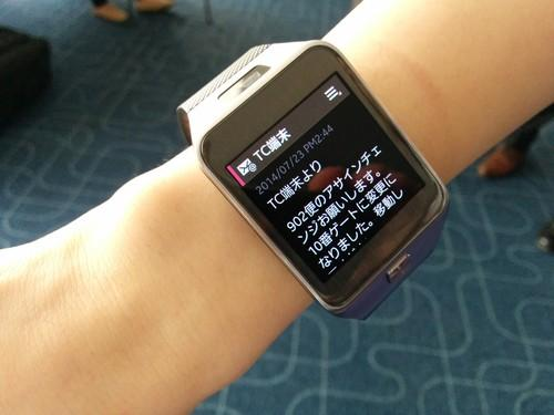 A Samsung Galaxy Gear 2 smartwatch displays information about a gate change during a Japan Airlines demonstration at Tokyo's Haneda airport.