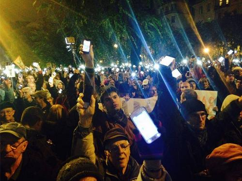 People in Budapest, Hungary hold up their phones during protest against a proposed Internet tax