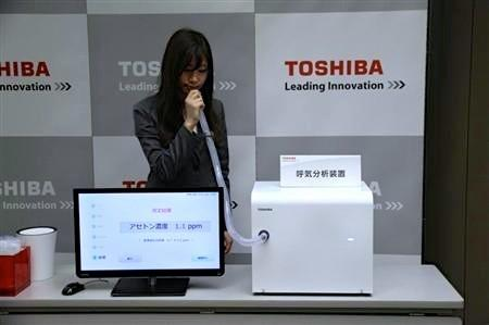 A woman tries a prototype medical breath analyzer developed by Toshiba. The company says it could help detect traces of medical conditions such as diabetes and is quicker and more compact than similar breath analysis machines.