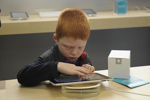 Wow! The new Apple iPad. A young Apple fan is mesmerised.