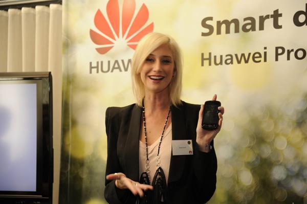TV host, Maude Garrett, holding a Huawei smartphone.