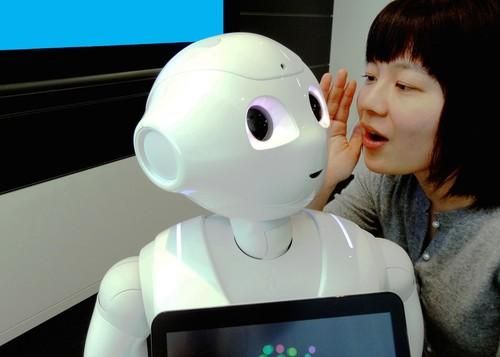 IBM researcher Risa Nishiyama poses with SoftBank's Pepper robot using Watson in a demonstration at IBM Research - Tokyo.