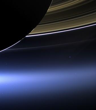 NASA's Cassini spacecraft took this image of Saturn and its rings with Earth in the background last week. Earth, which is 898 million miles away, appears as a blue dot at center right, while the moon can be seen as a fainter protrusion off its right side.